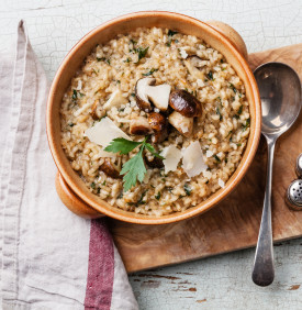 Risotto with wild mushrooms with parsley and parmesan on olive wood board