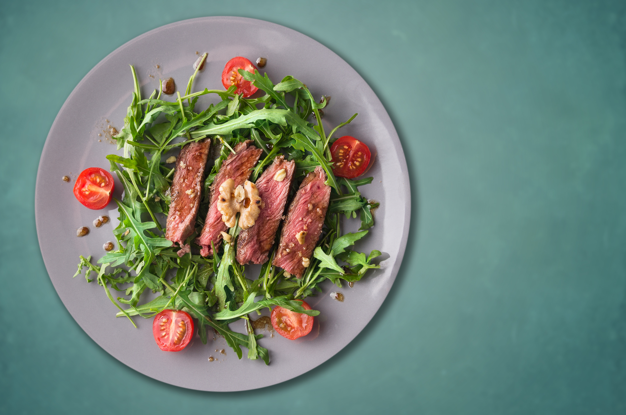 beef steak medium, Ruccola salad with tomatoes and walnuts,gray plate, blue background,copy space
