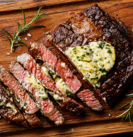 Sliced grilled Medium rare barbecue steak Ribeye with herb butter on cutting board close up