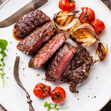 Sliced medium rare grilled Beef steak Ribeye with grilled onions and cherry tomatoes on plate on wooden background