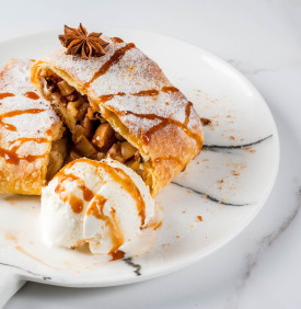 Home autumn, summer baking, puff pastries. Apple strudel with nuts, raisins, cinnamon and powdered sugar. On white marble table. Sliced, with ice cream and caramel topping. Copy space