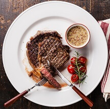 Sliced medium rare grilled Beef steak Ribeye with grilled cherry tomatoes and Pepper sauce on white plate on wooden background