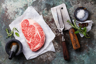 Raw fresh marbled meat Black Angus Steak Ribeye and seasonings on metal background
