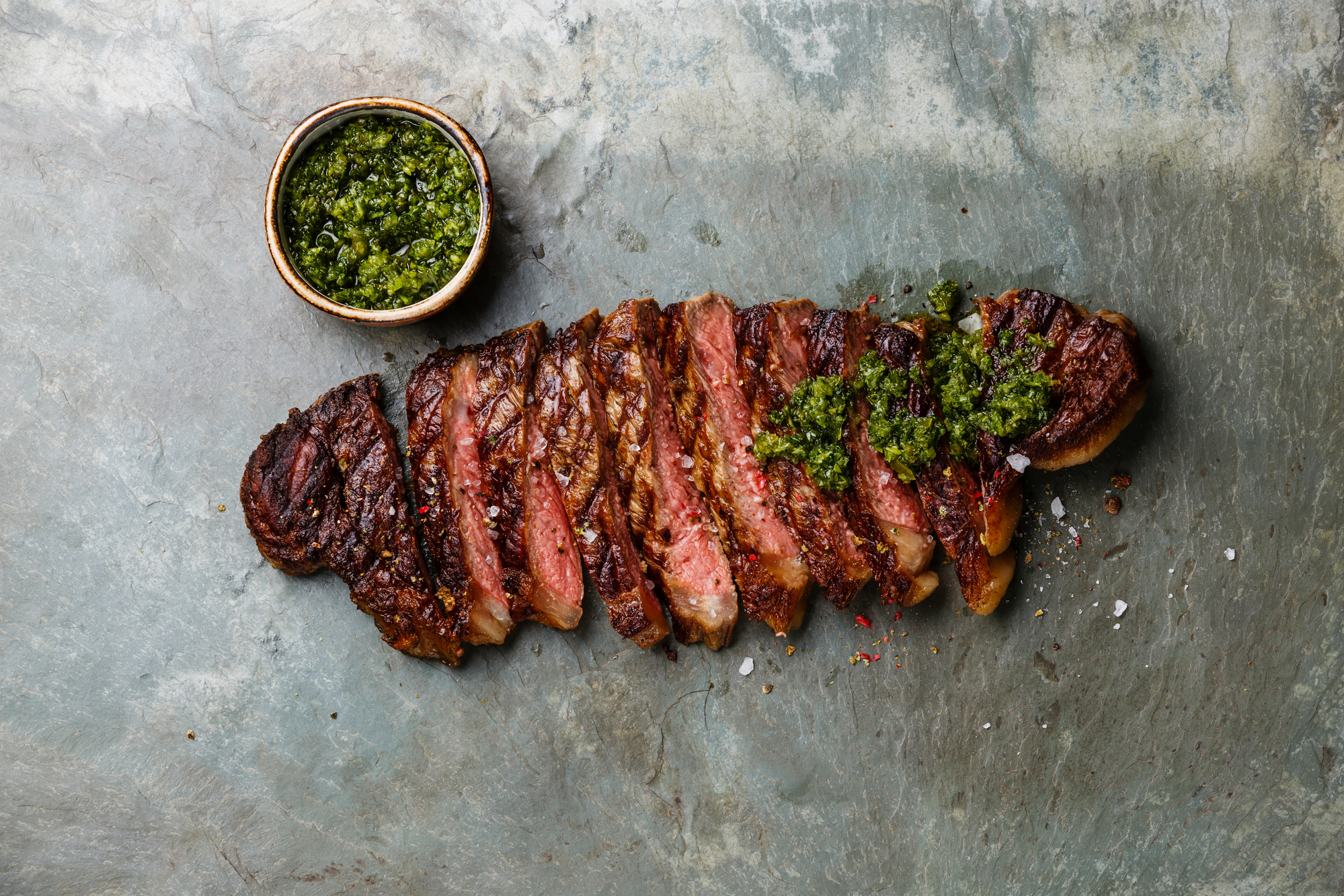 Sliced grilled beef barbecue Striploin steak with chimichurri sauce on gray stone slate background