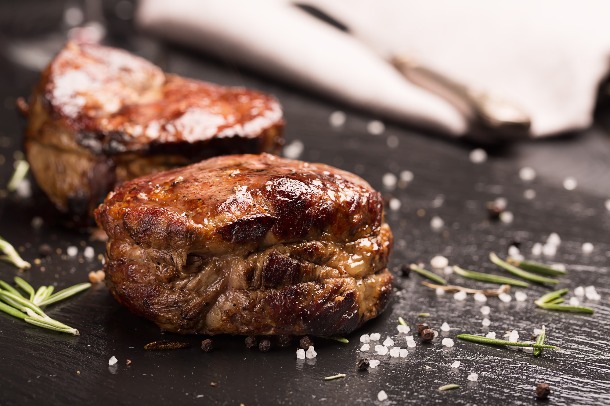 Grilled steak meat (mignon) on the dark surface. Dark background