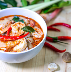 Tom yum kung, and condiment, on wooden table, Select focus